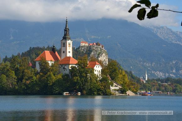 Slowenien, am Bleder See, Blick zur Marieninsel mit Kirche, dahinter die Burg von Bled.